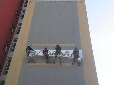 Pracownicy wysokościowi rozwieszający baner na bloku